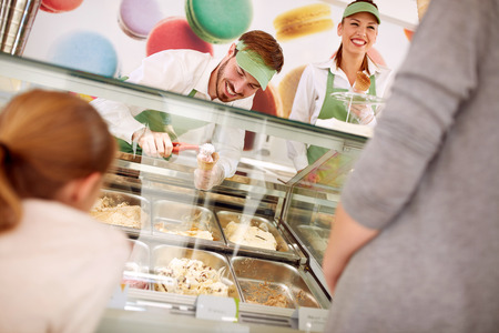 In pastry store sellers serves customers with ice cream