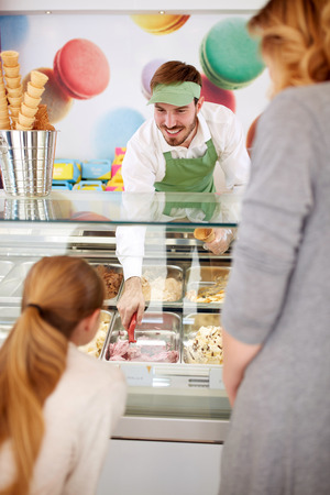 serviceable: Worker in pastry store serving girl with ice cream