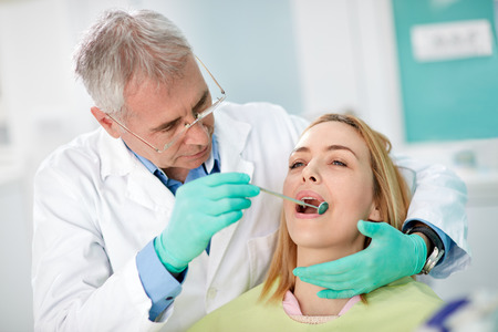 check up: Woman on dental check up in clinic Stock Photo