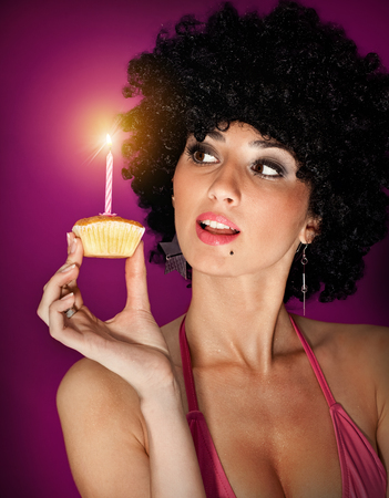 young sexy girl with small sweet cake on  color background photo