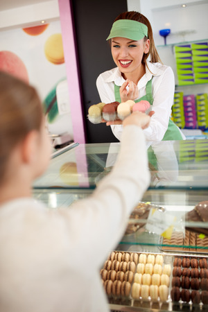 saleswoman: Smiling saleswoman gives macarons to young customer in bakery Stock Photo