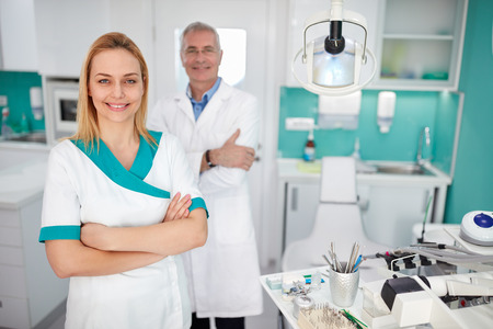 assistant: Portrait of pretty female dental assistant with dentist in dental clinic