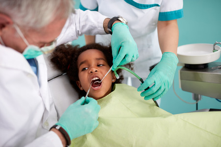 Black kid in chair on dental check up