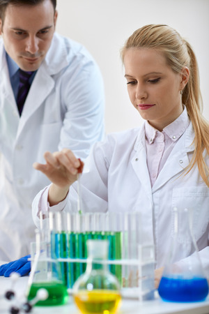 combining: female scientist combining the chemical liquid using a pipette in test tube
