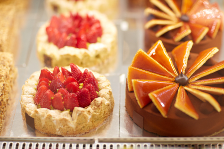 Different beautiful and tasty cakes in display case in pastry shop
