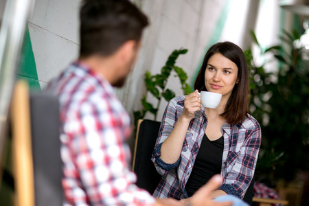 first date: Cute young woman drinking coffee on a first date