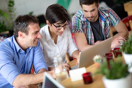 Feliz jóvenes empresarios que trabajan en la tienda de la computadora portátil en el café