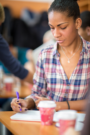 noting: Pretty Afro American student studying and noting on class Stock Photo