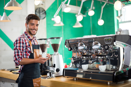 half dressed: Handsome barista offering a cup of coffee to camera in a cafe