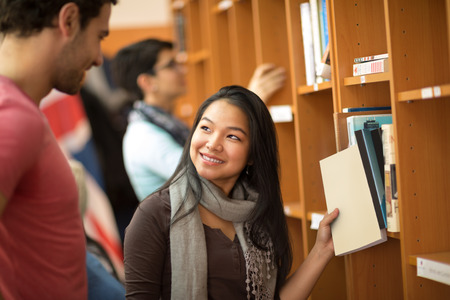choose university: Pretty Asian student choosing books with classmate in library