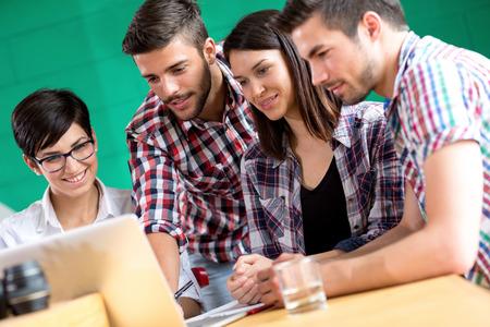 jovenes estudiantes: Los jóvenes estudiantes se comunican en café con la computadora portátil