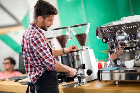 Satisfied barista steaming milk at coffee machine Foto de archivo