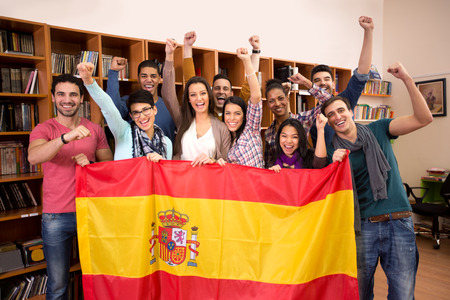 Team of excited Spanish students with victory smile and raised fists