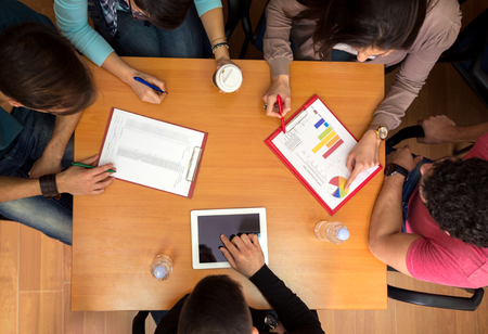 Top view of working table with students, tablet and statistics in teamwork Stock Photo
