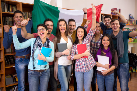 students: Smiling students with raised hands presenting Italy with flag