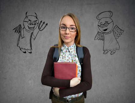 devil girl: Young nerd girl standing between the angel and devil drawings Stock Photo