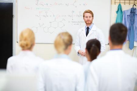 university professor: Young university professor studying students in front of blackboard