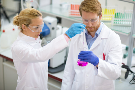 Young Chemist Taking Sample From Beaker In Lab Stock Photo, Picture ...