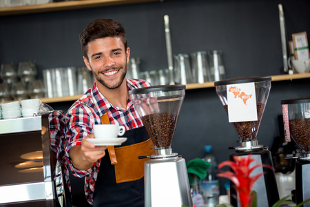 Handsome waiter offering a cup of coffee to customer