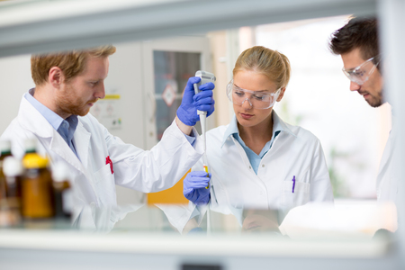 Three young chemical scientists place sample of fluid in test pipette
