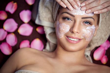 Glimlachende jonge vrouw op kuuroordbehandeling met gezichtsmasker