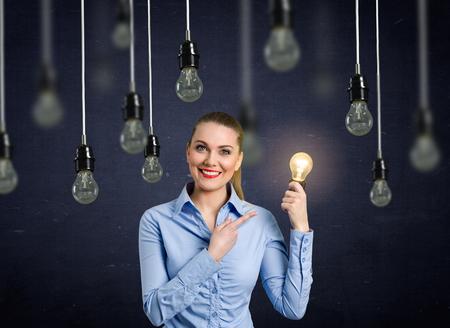Smiling girl holding a light bulb shining above her head hanging light bulbs that do not light up