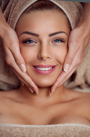 Spa woman, close-up of a young woman getting spa treatment, face massage Stock Photo