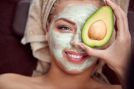 그녀의 얼굴에 자연 아보카도 마스크를 적용 젊은 여자의 초상화