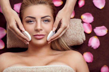 Beautician makes cleansing and exfoliating facial for beautiful girl. Beauty salon. Фото со стока