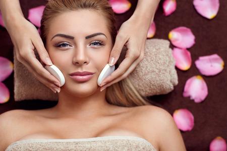 pulizia viso: Estetista fa pulizia ed esfoliante viso per la bella ragazza. Salone di bellezza.