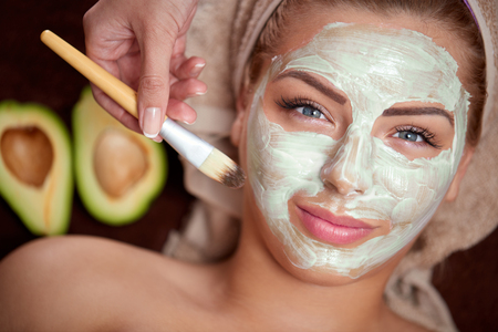 green avocado mask being applied at a beauty spa Stock Photo