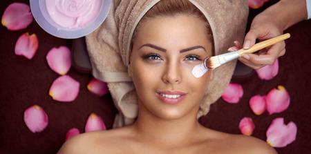 Cosmetician que aplica la máscara facial a la cara del joven y bella mujer en salón spa