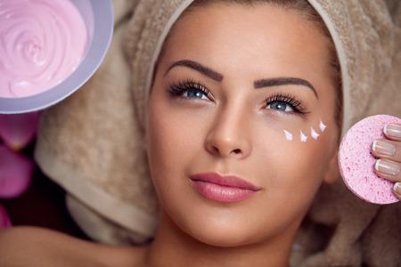 pulizia viso: Pretty giovane donna con la maschera facciale al Salone di bellezza Archivio Fotografico