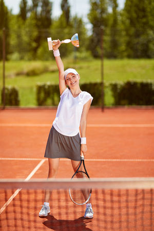 Young female tennis winner with goblet on tennis court Stock Photo