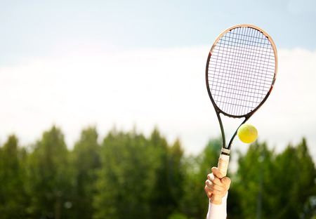 Close up of raised tennis racket and ball Stock Photo