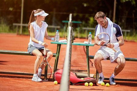 Young man and woman chatting on pause in tennis court Stock Photo