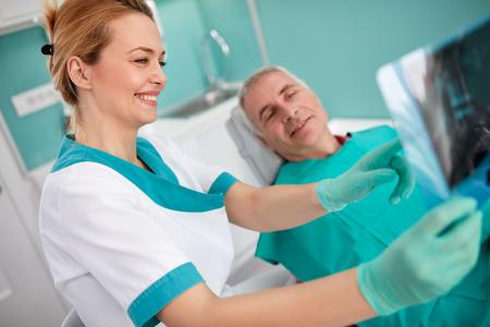 Le dentiste féminin montre un problème avec les dents sur les rayons X dentaires au patient Banque d'images