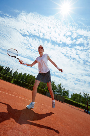 Sportswoman playing tennis at summer day