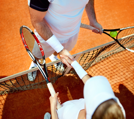 Male shaking hands with female before tennis training on tennis court