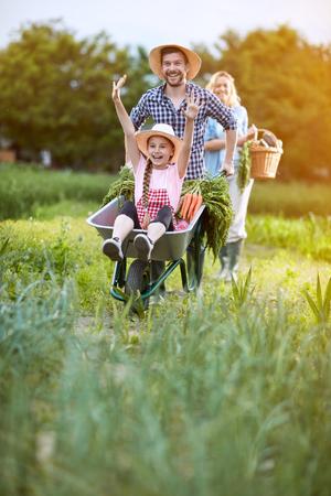 Vrolijk meisje genieten van kruiwagen Stockfoto