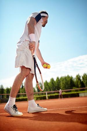 Sportsman play?s tennis in tennis court