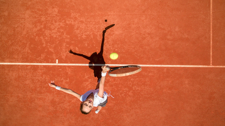 Young female tennis player hitting yellow ball on tennis terrain Stock Photo