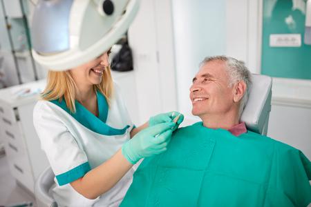 Vrouwelijke tandarts streeft naar de dichtstbijzijnde kleur van kunstgebit tanden naar mannelijke patiënt te vinden