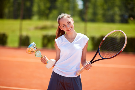 successes: Young female winner in tennis match holding goblet on tennis court