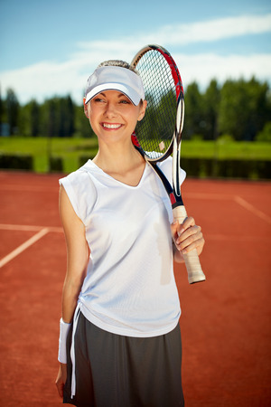 hitting: Girl with tennis racket picked up on tennis court Stock Photo