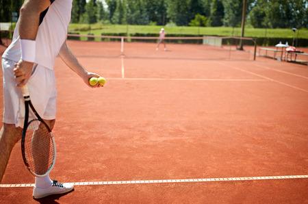 테니스 코트에서 테니스 공을 봉사 준비