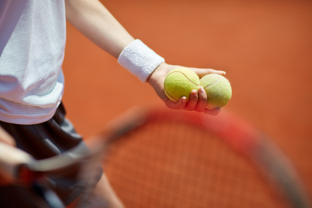 tennis clay: Close up of tennis balls in player's hand on tennis court Stock Photo