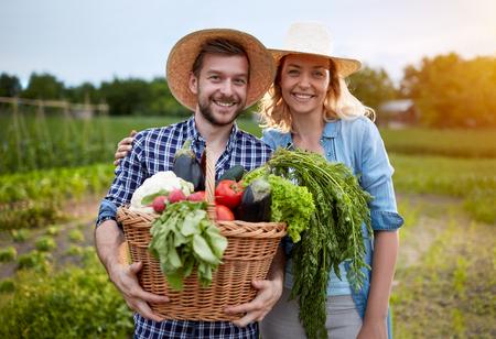 Pareja de agricultores en el jardín con la cesta llena de verduras Foto de archivo - 62461122