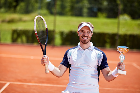 match: Male winner in tennis match with winner cup and racket Stock Photo