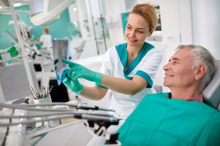 患者に歯科用 x 線の女性歯科医を示す歯問題 写真素材